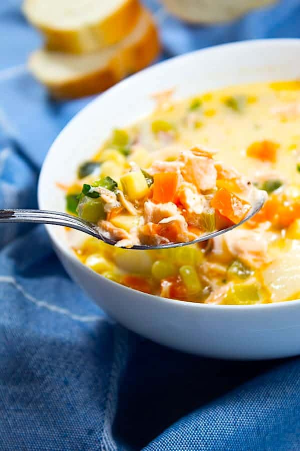 salmon chowder on a spoon with a white bowl of chowder in background