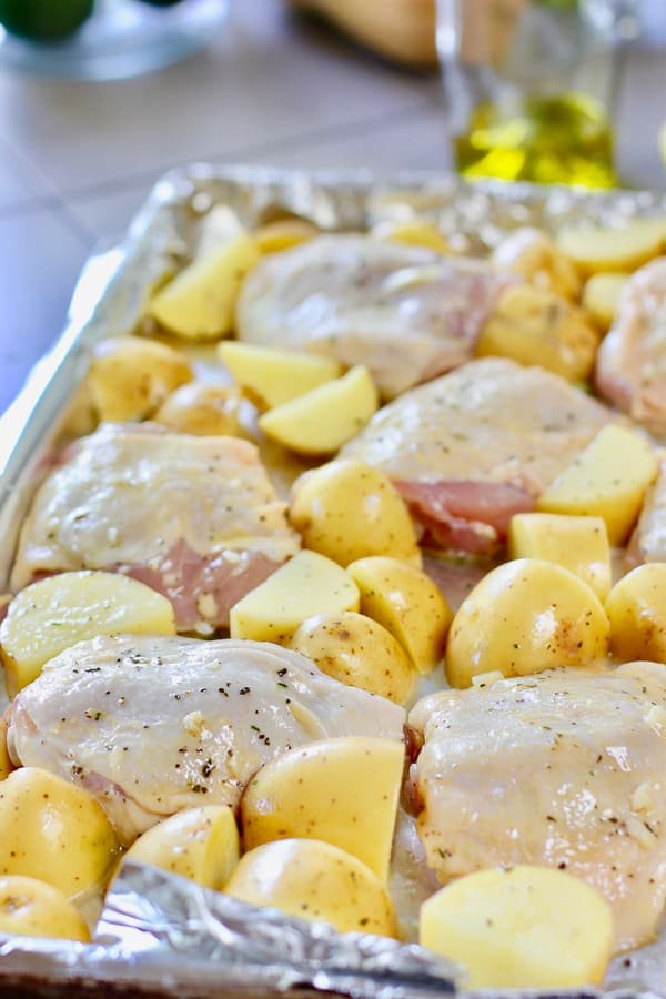 roasted chicken thighs and potatoes ready to go in the oven