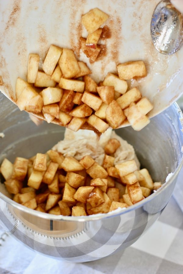 pouring diced apples into apple cake mixture