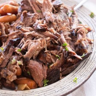 Tender slow cooker shredded pot roast on a cream colored plate