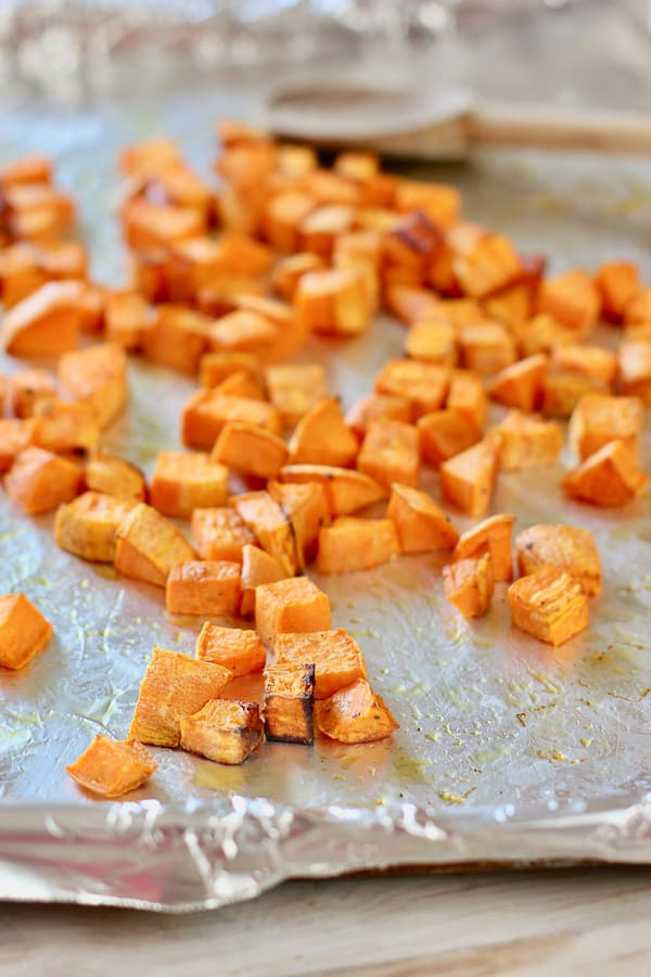 cubed roasted sweet potatoes on a sheet pan