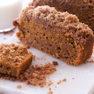 Pumpkin Loaf Cake cut into individual pieces on a white cutting board with crumbs