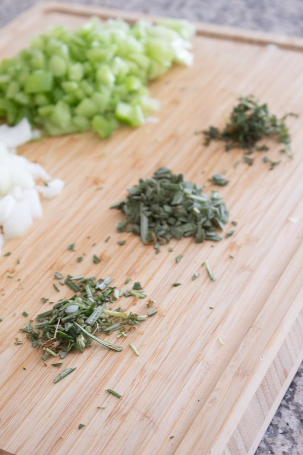 Chopped onion celery and herbs on a bamboo cutting board