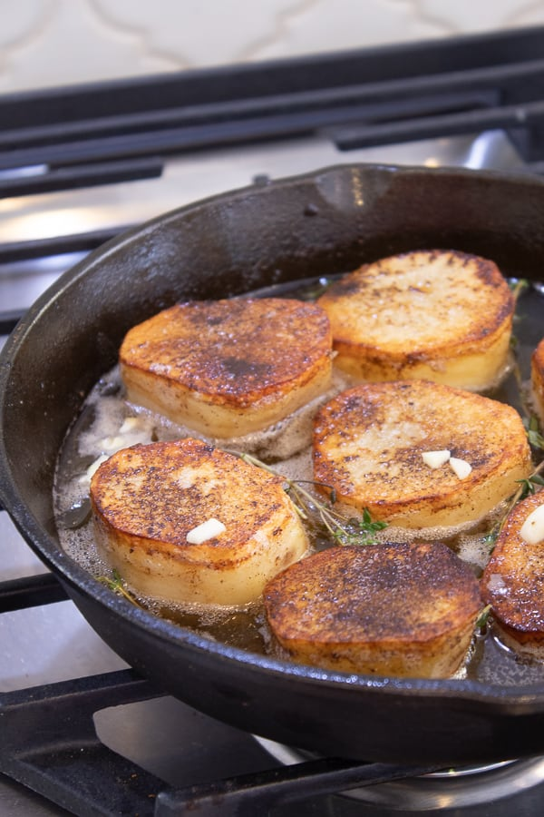 sliced fondant potatoes in cast iron skillet waiting for herbs