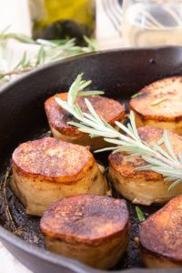fondant potatoes with rosemary garnish in a cast iron skillet