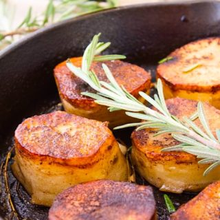 fondant potatoes in a cast iron skillet with a sprig of rosemary for garnish