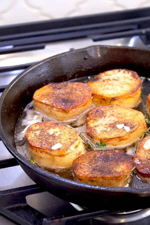 showing fondant potatoes cooking cast iron skillet with wine