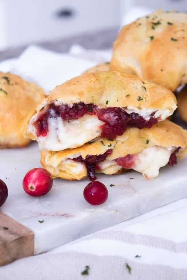 2 brie cranberry stuffed biscuits in half with gooey brie cheese
