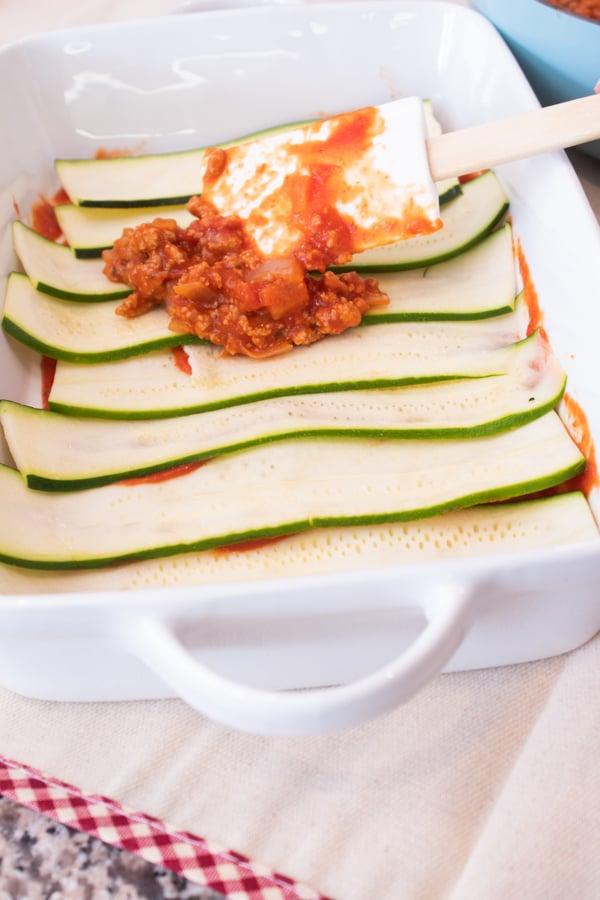 add meat sauce to zucchini lasagna in white casserole dish