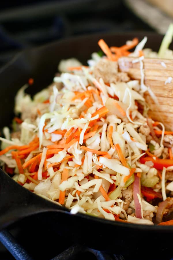 cabbage being added to egg roll bowl