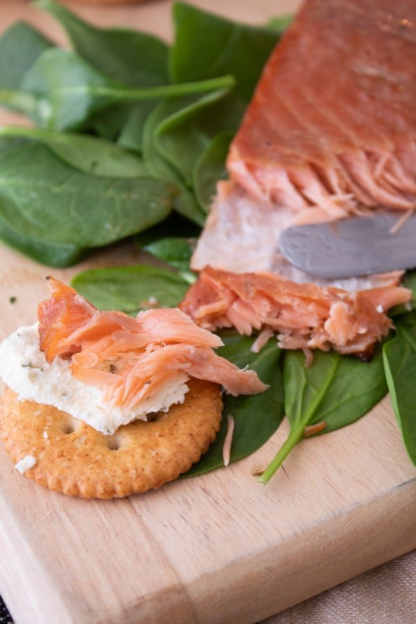 smoked salmon with crackers and cheese on a bed of spinach