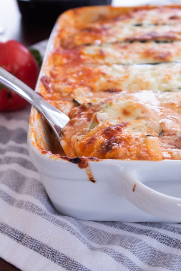 zucchini lasagna in a white casserole dish with a spoon coming out of it