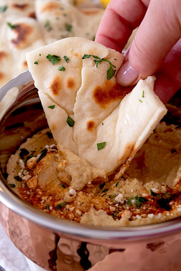 dipping naan in hummus