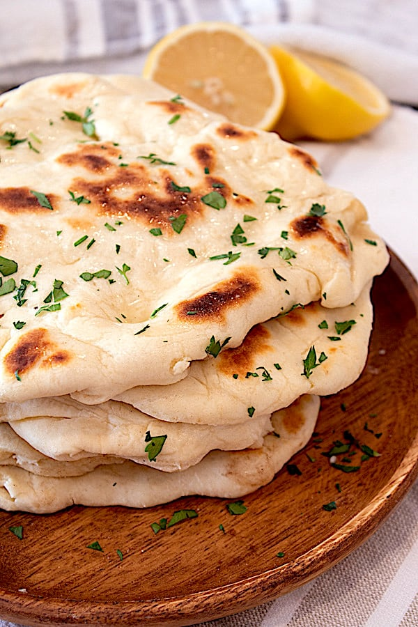 homemade naan on a wooden plate garnished with parsley