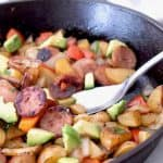 potato and sausage skillet topped with avocado
