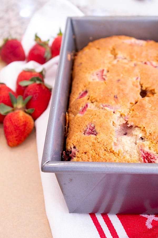 strawberry bread in loaf pan on red and white kitchen towel
