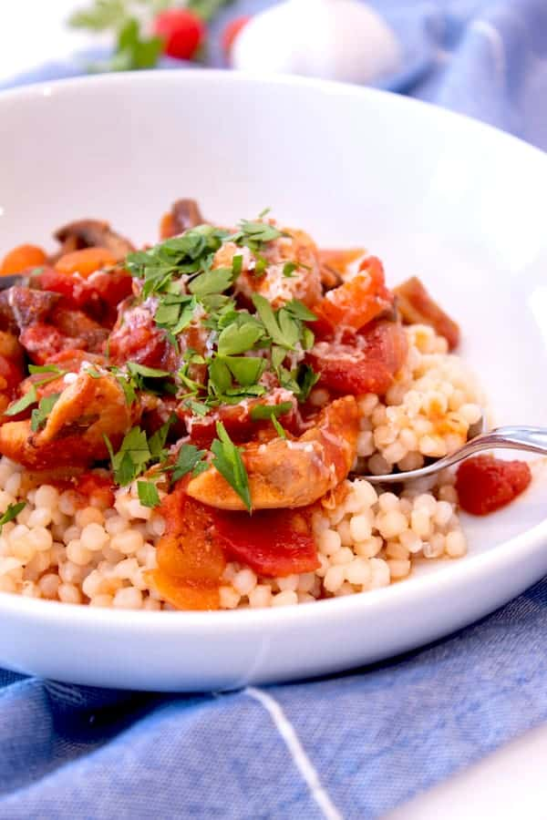 moroccan chicken stew in white dish over couscous
