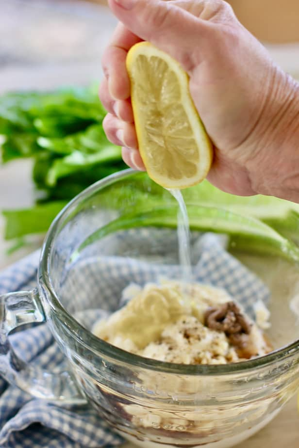 squeezing lemon into a clear bowl with caesar dressing ingredients