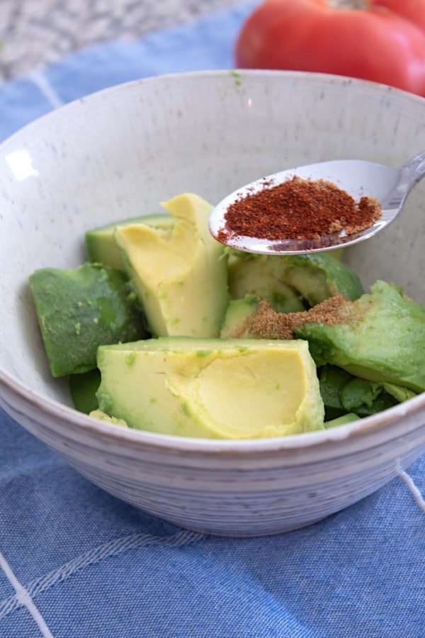 adding chili powder to bowl of avocado chunks