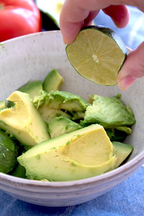 squeezing lime into guacamole