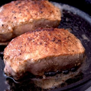 2 seared pork chops in a cast iron skillet