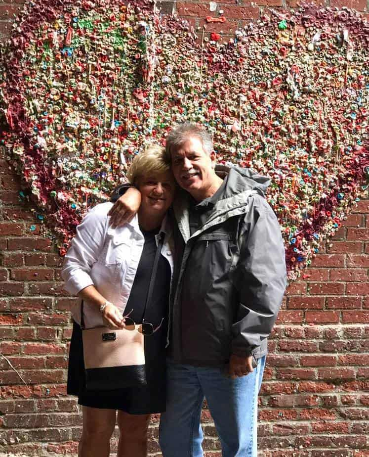 a couple in front of the Seattle gum wall