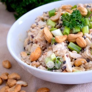 white bowl with asian rice salad in it garnished with parsley and whole cashews