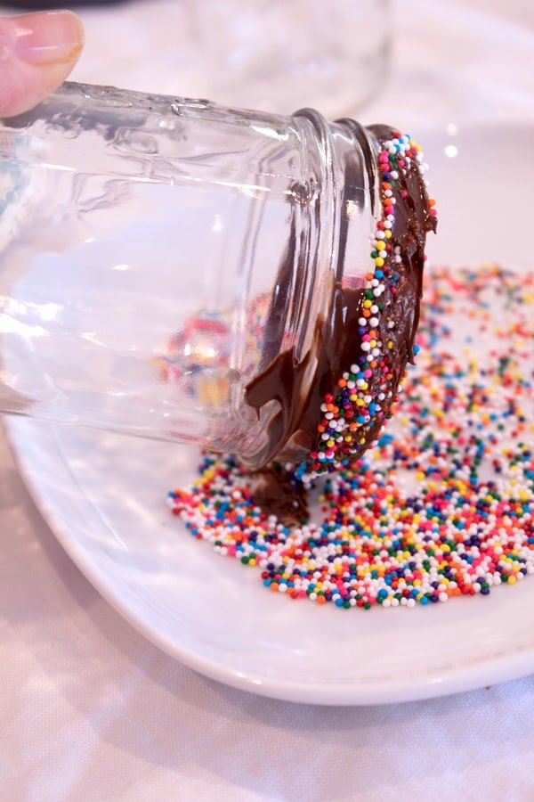 dipping a chocolate rimmed glass in a plate of colored nonpareil sprinkles