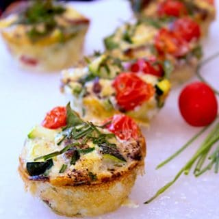 frittata muffins on a white cutting board with chives and red cherry tomatoes