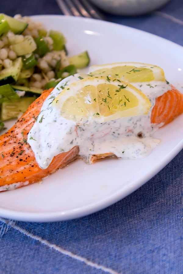 plated salmon with dill sauce on a white plate