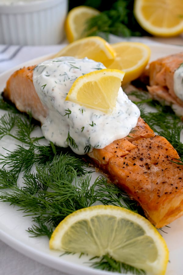 salmon filet with dill sauce on dill weed garnish with lemon