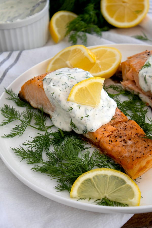 salmon and dill sauce on platter with dill and lemon garnish