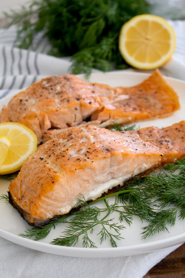 cooked salmon on a white plate with dill and lemon