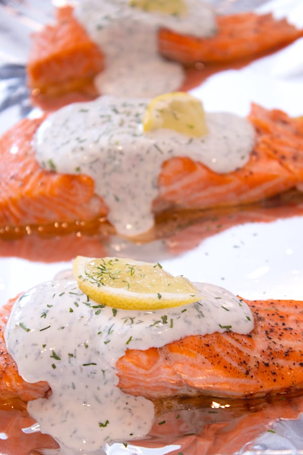 baked salmon on foil with dill sauce and a lemon wedge