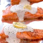 a foil lined pan with salmon dill sauce and a lemon wedge