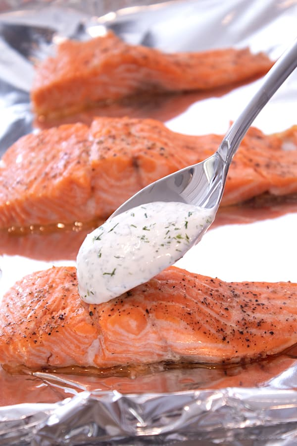 baked salmon with dill sauce being spooned on a filet