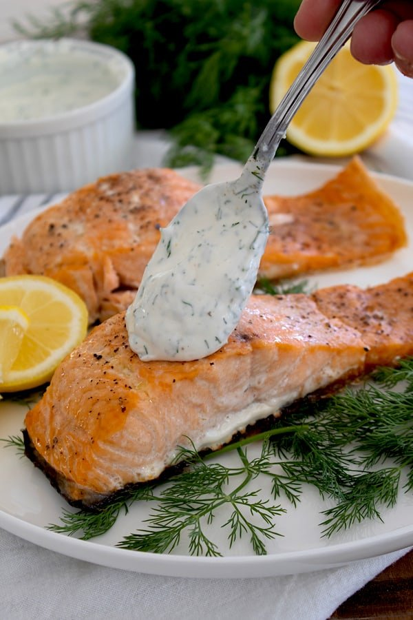 spooning dill sauce on salmon