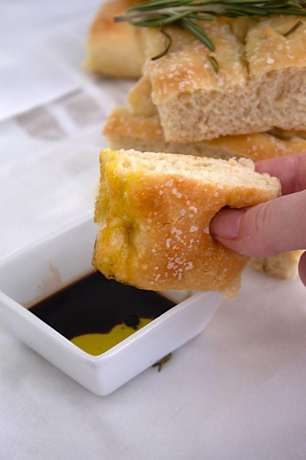 dipping focaccia bread in balsamic vinegar
