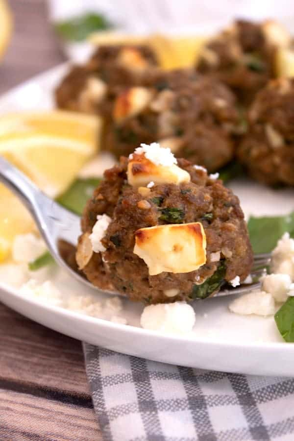 greek meatball with browned feta on a white plate with lemons and spinach in background