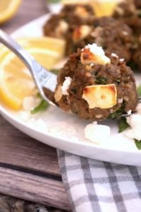 greek meatballs on a fork on a white plate with lemon and crumbly feta cheese