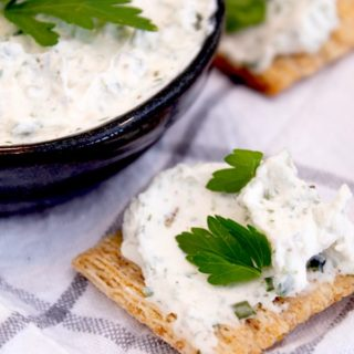 Boursin style cheese on a triscut cracker with fresh parsley on a white tea towel