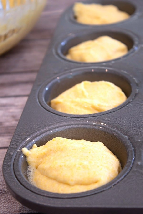 adding corn muffin batter to muffin tin with no liners