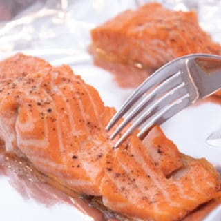 Salmon on a sheet pan being cut with a fork to show flakiness