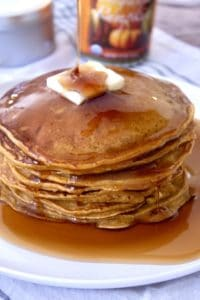 stack of pumpkin pancakes with butter and syrup on a white plate