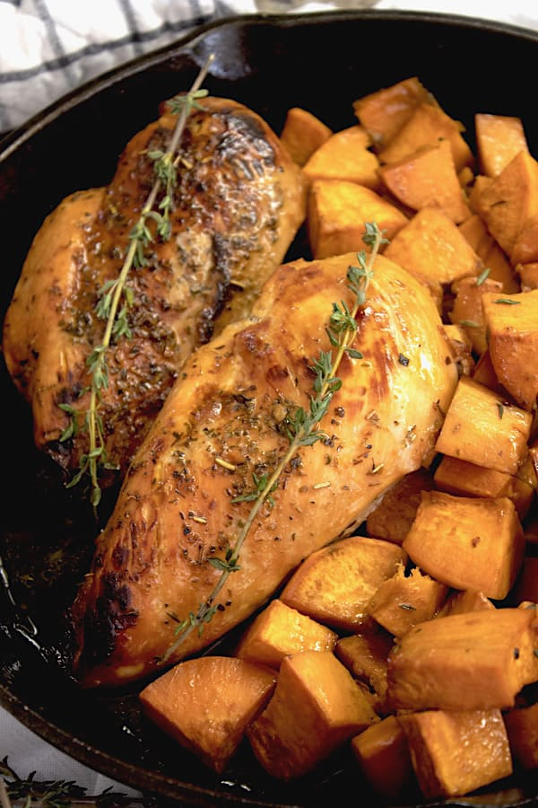 honey glazed chicken and sweet potatoes garnished with thyme in a cast iron skillet