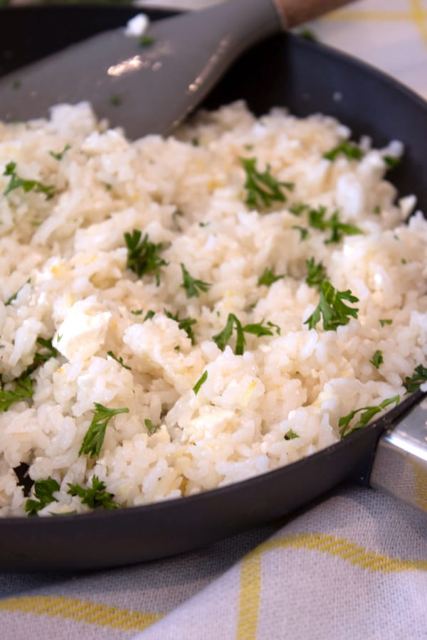 adding parsley to greek rice skillet