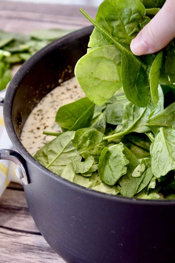 adding spinach to tortellini soup in a black pot