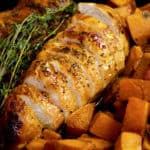 sliced honey glazed chicken with sweet potatoes garnished with thyme in a cast iron pan
