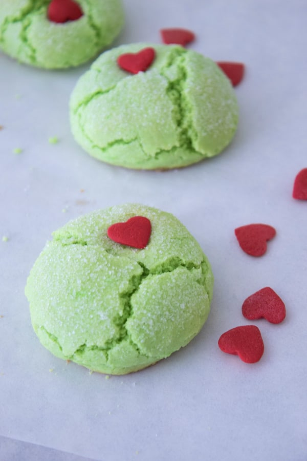 3 grinch green cookies on white parchment with red heart sprinkles