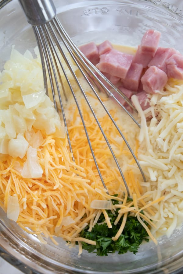 showing top of mixing bowl with onions, ham, cheese parsley and egg mixture